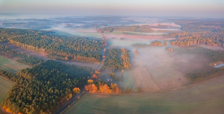 Beautiful foggy morning photographed from drone. Autumnal aerial landscape with fog over land. Zdjęcie Seryjne