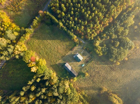 Farm or house in autumnal forest, top down aerial landscape.