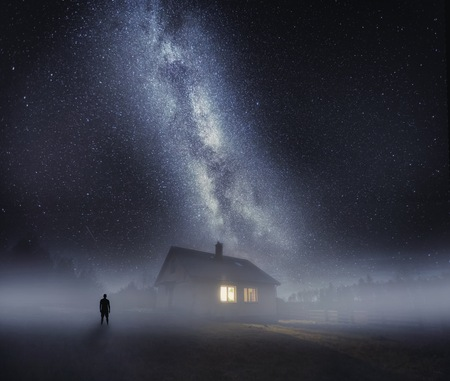 Surreal night landscape with house in fog and human silhouette under starry sky. Dreamy look. Stock Photo
