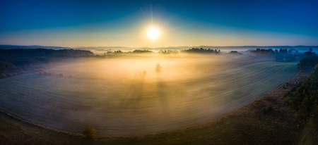 Beautiful foggy morning photographed from drone. Autumnal aerial landscape with fog over land. Stock Photo