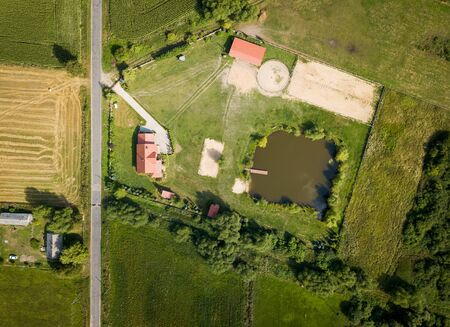 Top down drone landscape with buildings on fields. Farm from above.
