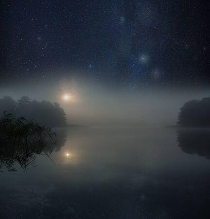 Nigh spooky landscape with foggy lake under satrry sky.