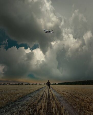Man standing on empty field under dark cloudy sky with plane. Surreal landscape.