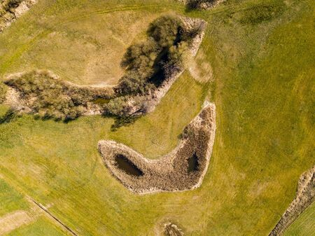 Top down aerial view with early spring meadows, pond and river. Polish landscape.