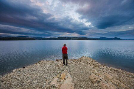 Man standing on lake shore under dark sky. Solinskie lake in Bieszczady mountains
