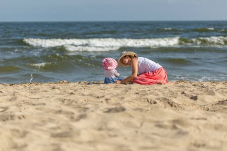 Mother with small baby girl relaxing on sea beach at sunny summer day. Zdjęcie Seryjne