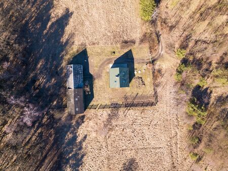 Farm in early spring forest photographed from above. Top down aerial landscape.