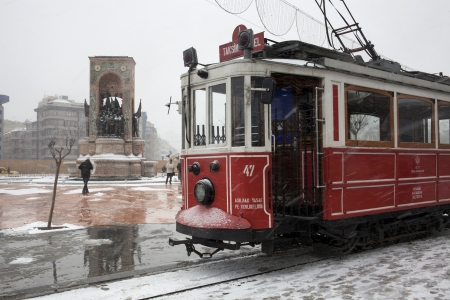 Istanbul, Taksim, Turkey - January 8, 2013 -  Nostalgic tram when snowfalls at Istanbul,Taksim,Turkey. At the left Monument of Republic and Taksim Square
