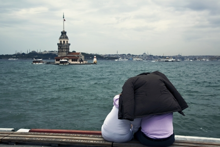 Istanbul, Uskudar, Turkey - September 09, 2011 - Couple watching The Maiden's Tower at Istanbul,Turkey. They are protecting theme selves from the rain by using the mans coat. Istanbul City and The Bosphorus at the picture too. Stock Photo - 18322029