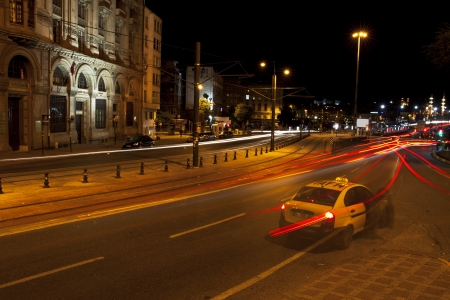 Istanbul, Karakoy, Turkey - May 29, 2012  A customer geting on to a taxi  Only cars lights are visible at the long exposure image and some historical buildings at Istanbul,Karak�y District,Turkey