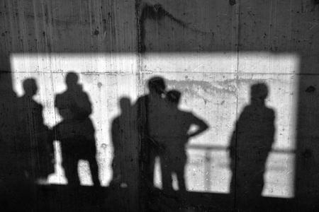 personas: Hombres sombras en la pared de hormig�n.