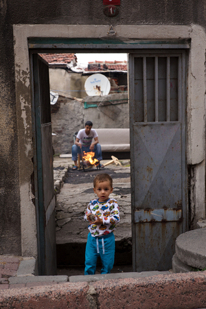 turquia: Estambul, Turqu�a - el 23 de de agosto de, 2015: refugiados sirios en Estambul, Turqu�a. El peque�o ni�o de pie en frente de una casa en ruinas y que mira inocente y que sostiene una piedra como un juguete.