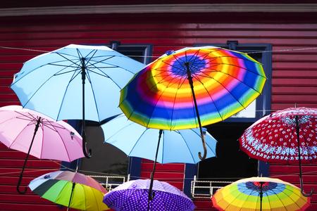 Strada con ombrelli colorati di fronte a una casa di legno rosso. Archivio Fotografico