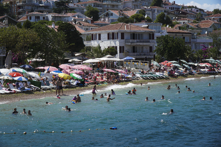 Istanbul, Turkey - August 6, 2016: People are swimming and sunbathing at The Kinaliada Beach near Jetty Editorial