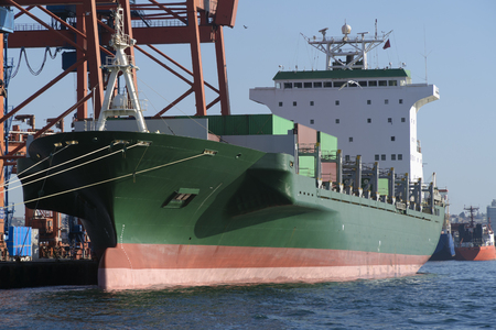 unloading: Huge green cargo container ship at dock was unloading its cargo in a sunny day Stock Photo
