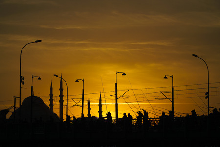 Silhouettes of Some Anglers and The Suleymaniye Mosque At The Galata Bridge in Istanbul After Sunset