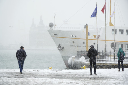turkish ethnicity: Istanbul, Turkey - January 7, 2017: People are watching the scenic at Kadikoy in a snowy day with a traditional public transportation ship and The Haydarpasa Train Station Building at the background.