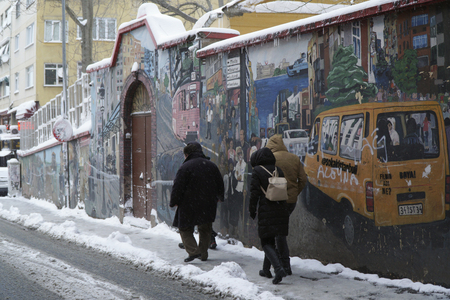 turkish ethnicity: Istanbul, Turkey - January 7, 2017: A famous street from Istanbul Kadikoy in a snowy day with people and a beautiful wall art.