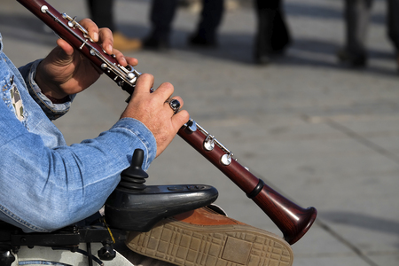 Man hands are playing a wooden clarinet