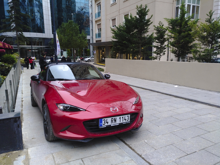 Istanbul, Turkey - February 2, 2018: A red new Mazda MX-5 at Istanbul, Kadikoy, Caddebostan District at street with some people and stores.