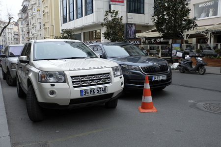Istanbul, Turkey - February 24, 2018 : A beige Land Rover with new Skoda Karoq  were parked at The Nisantasi Tesvikiye Street at Istanbul. There are stores and cafes at the background with some people