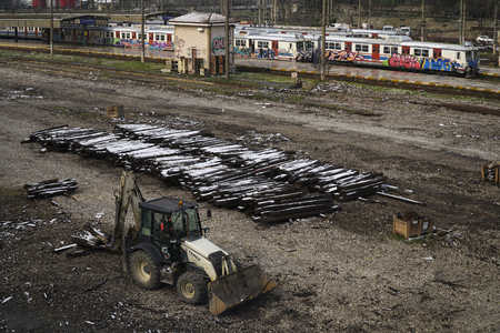 Istanbul, Turkey - March 1, 2018 : A parked buldozer is waiting for working hour. There is a major restoration at the railroad tracks. Old lumbers covered with snow and trains covered with graffiti Editorial