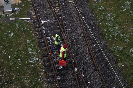 Istanbul, Turkey - March 1, 2018 : Two railroad workers or engineers are walking on the rails at Istanbul, Kadikoy. Theye are carrying equipments. Editorial