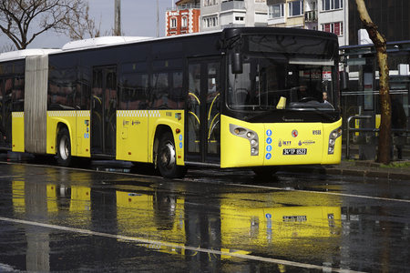 Istanbul, Turkey - March 3, 2018 : A public transportation bus is waiting for passengers at The Istanbul, Kadikoy main bus terminal. Reflections on the wet asphalt road are perfect. Editorial