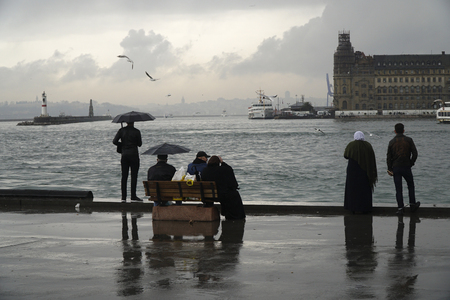Istanbul, Turkey - March 8, 2018 : Rainy day at The Istanbul, Kadikoy seaside. Some people are watching The Istanbul Landscape with The Haydarpasa Train Station Building and jetty with lighthouse.