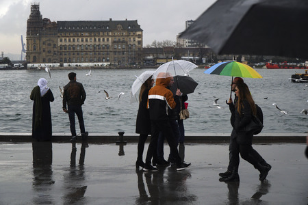 Istanbul, Turkey - March 8, 2018 : Rainy day at The Istanbul, Kadikoy seaside. Some people are walking with umbrellas, orthers are watching The Haydarpasa Train Station landscape.