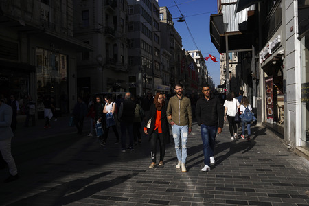 Istanbul, Turkey - April 19, 2018: Arap ethnicity tourists are walking at The Istiklal Street, Beyoglu in a sunny springtime day. There are many stores are visible at the street. Editorial