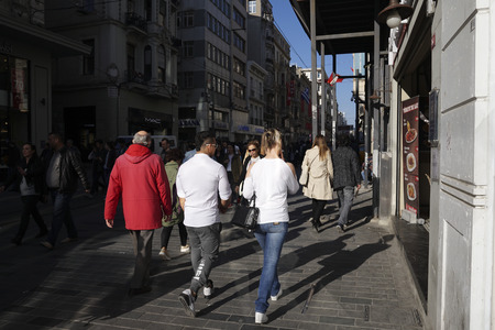 Istanbul, Turkey - April 19, 2018: Turkish people and  tourists are walking at The Istiklal Street, Beyoglu in a sunny springtime day. There are many stores are visible at the street.