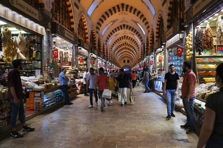 Istanbul, Turkey - May 17, 2018: The Famous Spice Bazaar in Istanbul with shopping tourists and shopkeepers. Arabian tourists are carrying shopping bags.