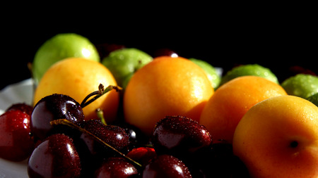 Wet plums, apricots and cheeries at black backgrounds