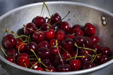Wet cherries are in a sieve Stock Photo
