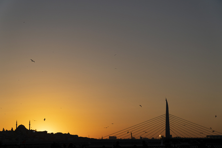 Historical and modern architecture together At Istanbul Sunset. There is a historical mosque at the left side and The Subway Bridge at the right side of the image. There are cables of trams at the top. Stock Photo