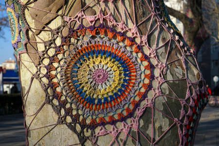 Spectacular handmade colorful knitted ornament on a tree trunk.