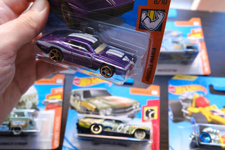Istanbul, Turkey - July 12, 2020: A Hot Wheels purple American custom diecast toy car from Muscle Mania serie on hand and others at the background on a table. 新闻类图片