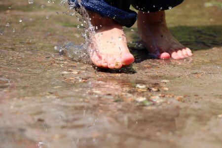 Barefoot boy runs through the puddles