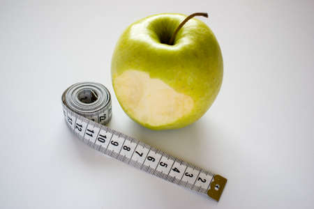 Bitten green apple with measuring tape on white background