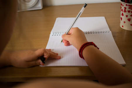 Close up of little blond girl drawing at desk Фото со стока
