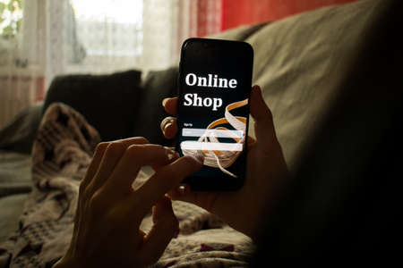 Close up female hands holds smartphone lying in bed under warm blanket in morning. Buying online concept 版權商用圖片