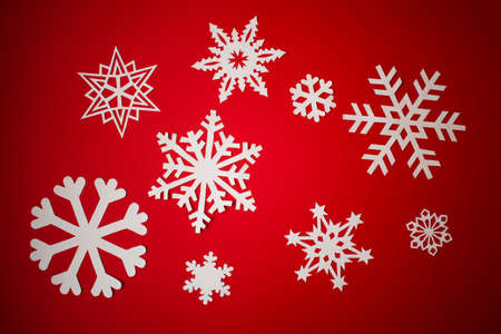 Various paper cut out snowflakes on red background Zdjęcie Seryjne