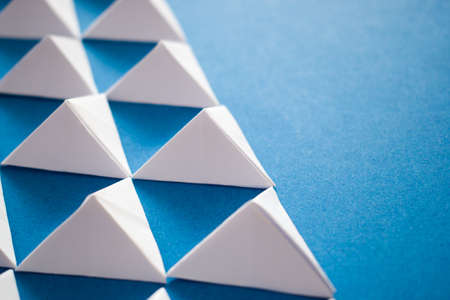 Close up of white paper triangles on blue background