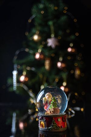 Christmas scene with tree, lights and snow globe. Selective focus on black background.