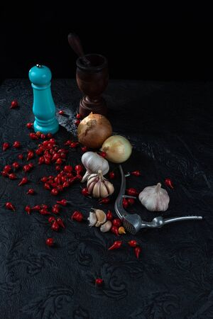 Peppers, olive oil and wooden mortar and more accessories on black background.