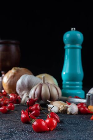 Peppers, olive oil and wooden mortar and more accessories on black background with selective focus