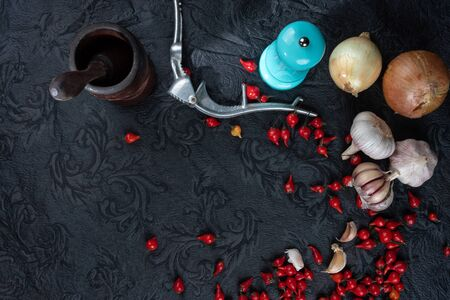 Peppers, olive oil and wooden mortar and more accessories on black background. top view Reklamní fotografie