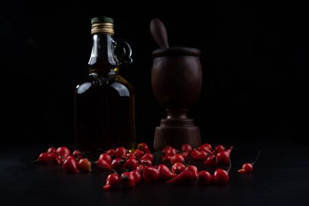 Peppers, olive oil and wooden mortar on black background, selective focus