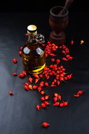 Peppers, olive oil and wooden mortar on black background top view